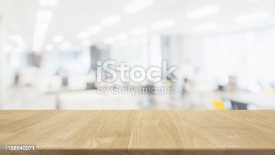 istock Empty wood table top and blur glass window wall in office building space interior background - can used for display or montage your products. 1158540071