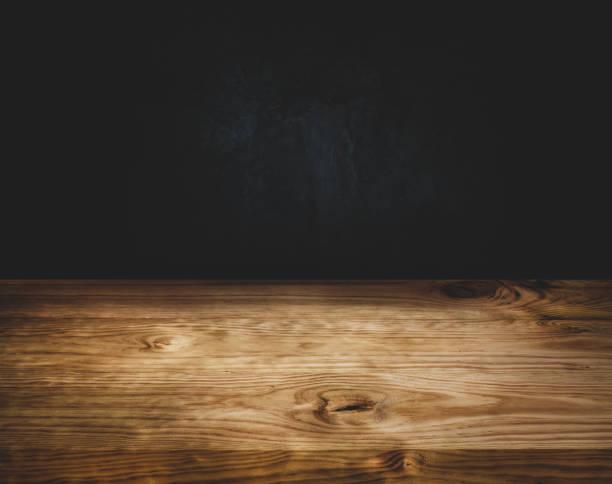 leere holz tischplatte zähler auf dunklen wand hintergrund - tresentisch stock-fotos und bilder
