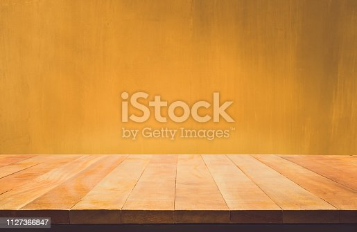 593305530istockphoto Empty wood table top counter on dark yellow  wall background.For create product display or design key visual 1127366847