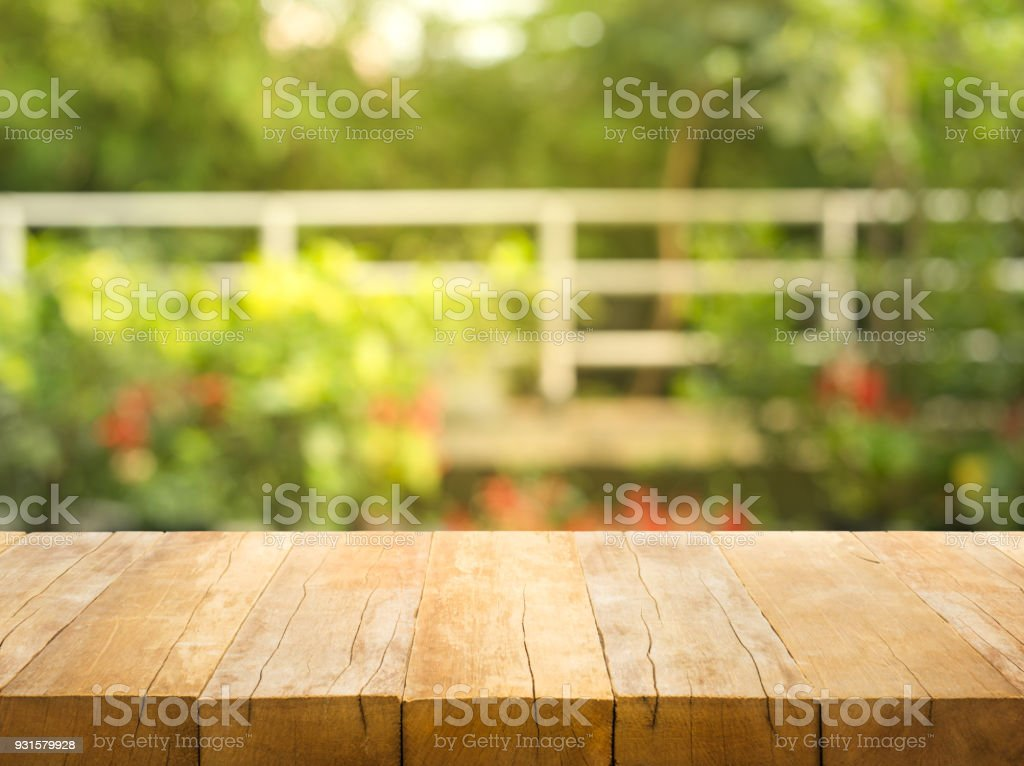 Empty wood table top on blur abstract garden and house background stock photo