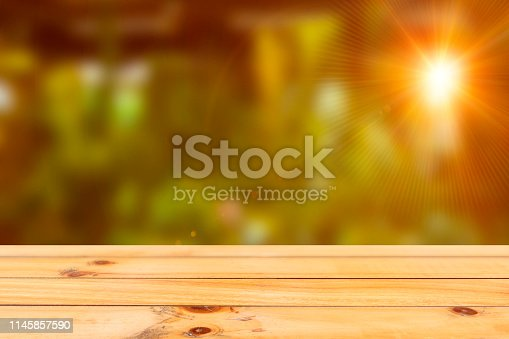 Empty wood table top on blur abstract green from botanic gardens background