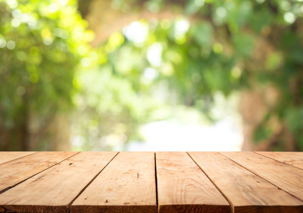 Empty wood table top on blur abstract green from garden and home area background stock photo