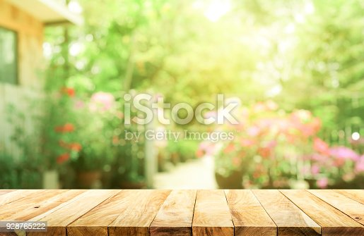 680878382istockphoto Empty wood table top on blur abstract green from garden and house background 928765222