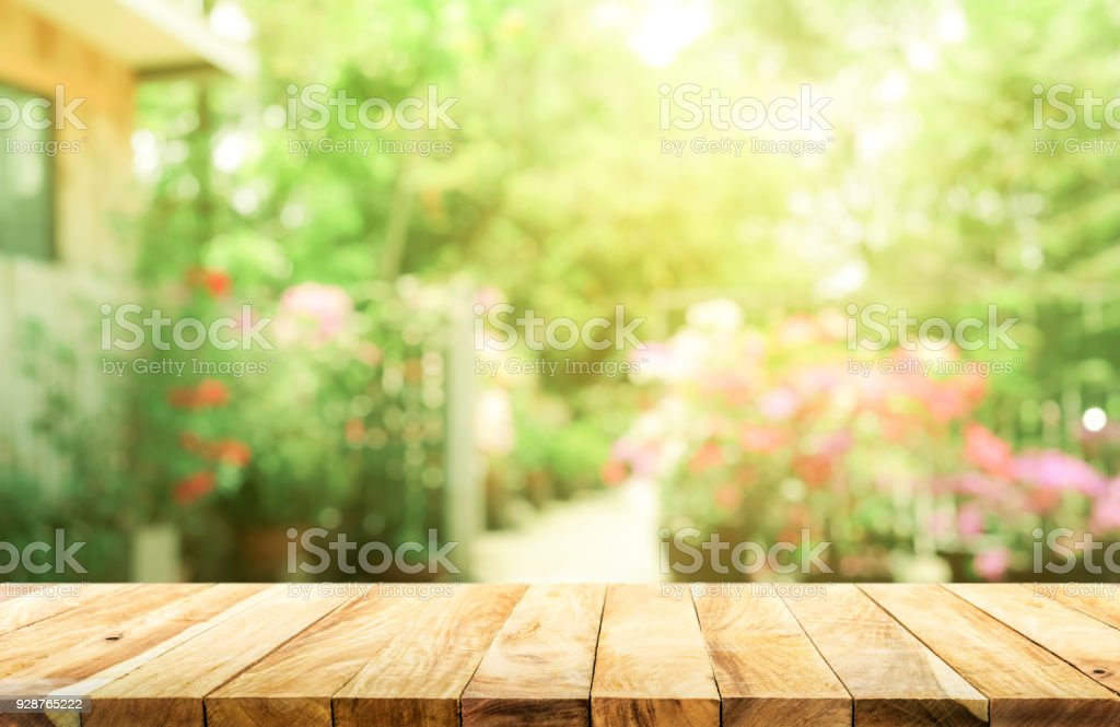 Empty wood table top on blur abstract green from garden and house background stock photo