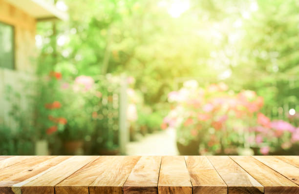 empty wood table top on blur abstract green from garden and house background - soleggiato foto e immagini stock