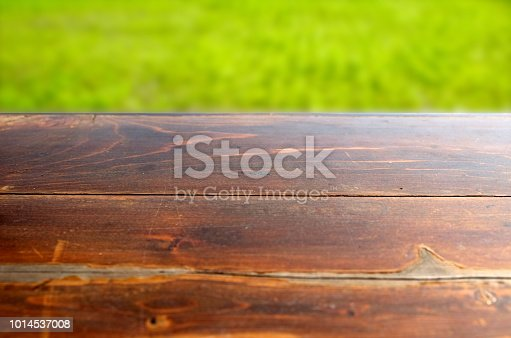 862429776 istock photo Empty wood table top on blur abstract green from garden in morning background. can be used for display or montage your products 1014537008