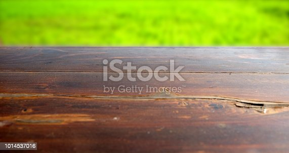 862429776 istock photo Empty wood table top on blur abstract green from garden in morning background. can be used for display or montage your products 1014537016