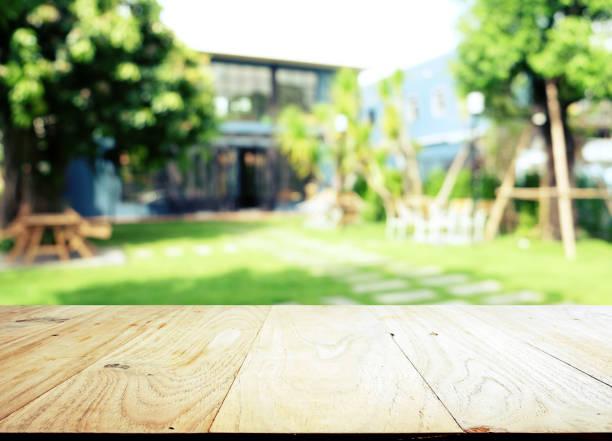 leere holztischplatte auf unscharftes abstraktes grün aus garten im morgenhintergrund. kann für die anzeige oder montage ihrer produkte verwendet werden - terrasse grundstück stock-fotos und bilder