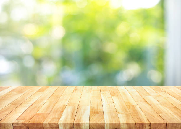 Empty wood table top on blur abstract green garden from window view in the morning. For montage product display or design key visual stock photo