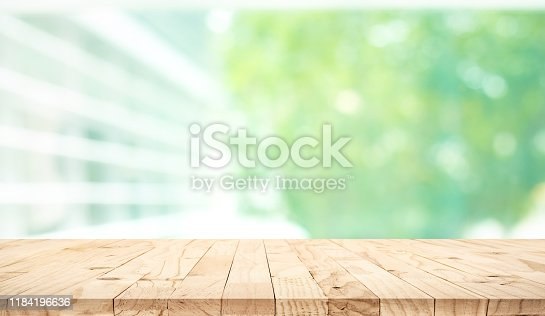 641254964 istock photo Empty wood table top on blur abstract green garden from window view background 1184196636