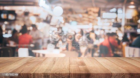 924418708 istock photo Empty wood table top on blur light bokeh in dark night cafe restaurant background 1183793249