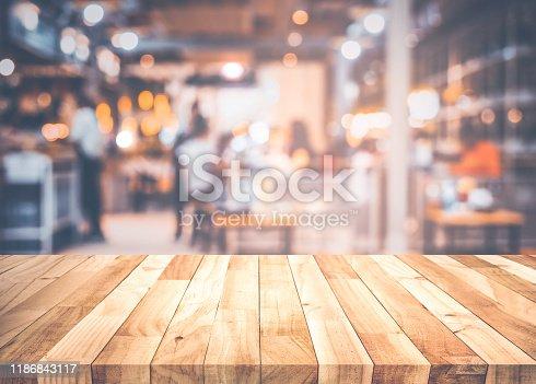 924418708 istock photo Empty wood table top on blur light bokeh in dark night cafe restaurant background 1186843117