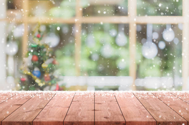 empty wood table top on blur with bokeh christmas tree and new's year decoration on window background with snowfall - can be used for display or montage your products. - christmas table foto e immagini stock