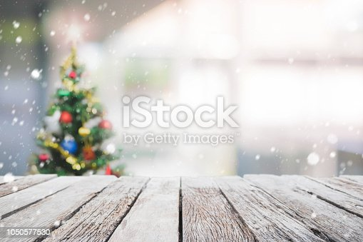 istock Empty wood table top on blur with bokeh Christmas tree background with snowfall - can be used for display or montage your products. 1050577530