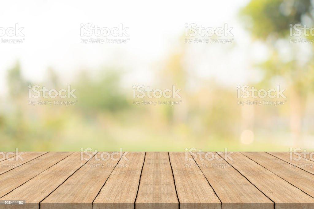 Table en bois vide haut sur fond de nature vert floue au jardin