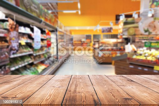 istock Empty wood table top on shelf in supermarket blurred background 1002918312
