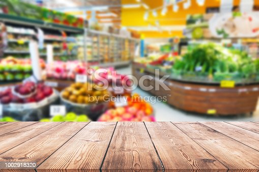istock Empty wood table top on shelf in supermarket blurred background 1002918320