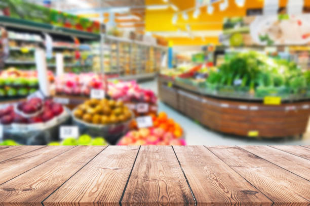 Empty wood table top on shelf in supermarket blurred background stock photo