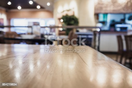 886308526 istock photo Empty wood table top with blurred cafe restaurant coffee shop interior background 854219834