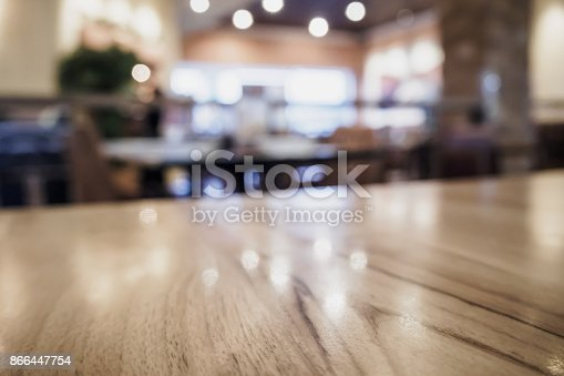 886308526 istock photo Empty wood table top with blurred cafe restaurant coffee shop interior background 866447754