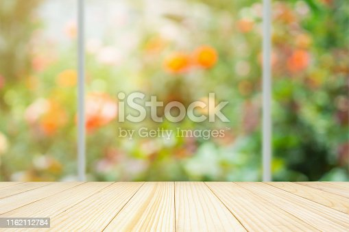 680878382 istock photo Empty wood table top with kitchen window abstract blur colorful rose flowers in the garden natural bokeh light background 1162112784