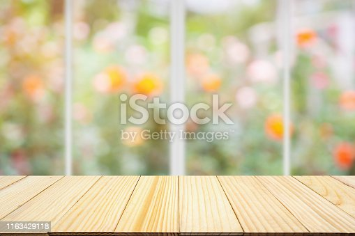 680878382 istock photo Empty wood table top with kitchen window abstract blur colorful rose flowers in the garden natural bokeh light background 1163429118