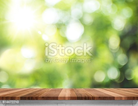 885452818istockphoto Empty wood table top with sun and blur green tree 514472210