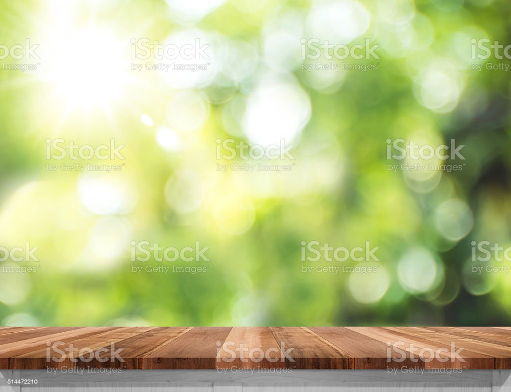 Empty wood table top with sun and blur green tree stock photo