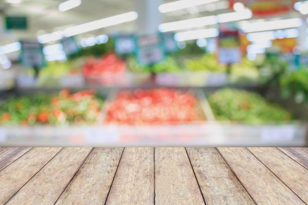 leere holz tischplatte mit supermarkt hintergrund unscharf - gemüsefond stock-fotos und bilder