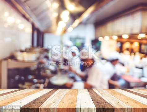 886308526istockphoto Empty wood table with blur open cooking restaurant background,Mo 515594998