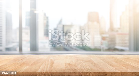Empty wood table with blur room office and window city view background.For montage product display or design key visual layout.