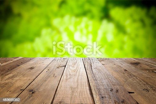 Empty wood table with defocused green foliage at background, spotlight effect at the center of the frame. Ideal for product display on top of the table
