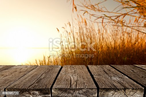Empty rustic wood table with defocused sunset at background. Ideal for product display on top of the table. DSRL studio photo taken with Canon EOS 5D Mk II and Canon EF 24-105mm f/4L IS USM Telephoto Zoom Lens