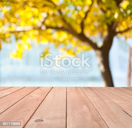 Empty wood table with defocused yellow foliage tree at background, spotlight effect in the center of the frame. Ideal for product display on top of the table