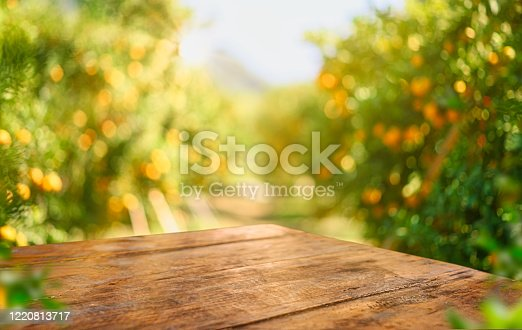 istock Empty wood table with free space over orange trees, orange field background. For product display montage 1220813717