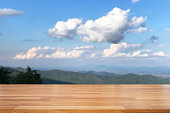 istock Empty wooden and table on abstract nature view with cloud, blue sky, leaf and mountain background 1126359600