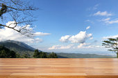 istock Empty wooden and table on abstract nature view with cloud, blue sky, leaf and mountain background 1126359604