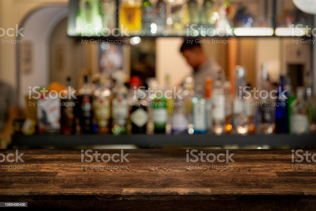 Empty dark wooden bar counter with bottles of restaurant, bar or...