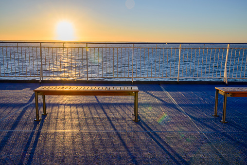 Empty wooden bench in ferry boat at sunset.