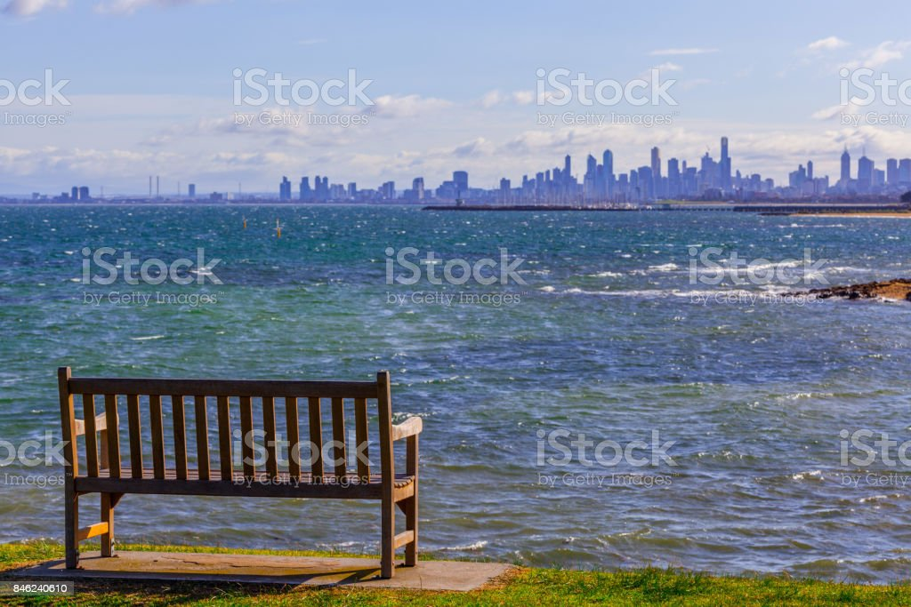 Empty wooden bench on ocean shore overlooking the skyline of Melbourne CBD on bright sunny day stock photo