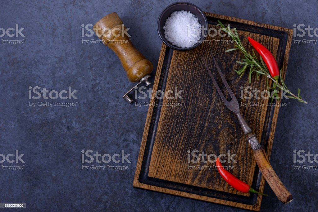 Empty wooden board and chili pepper, rosemary, salt stock photo