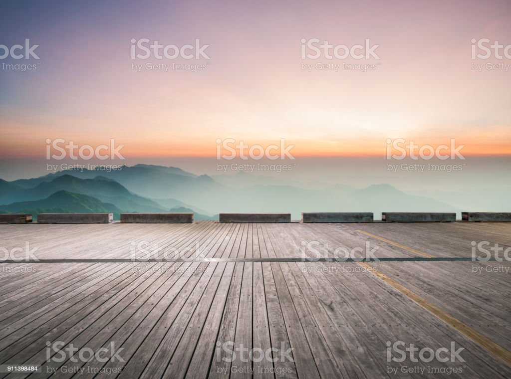 empty wooden board front of mountain ranges stock photo