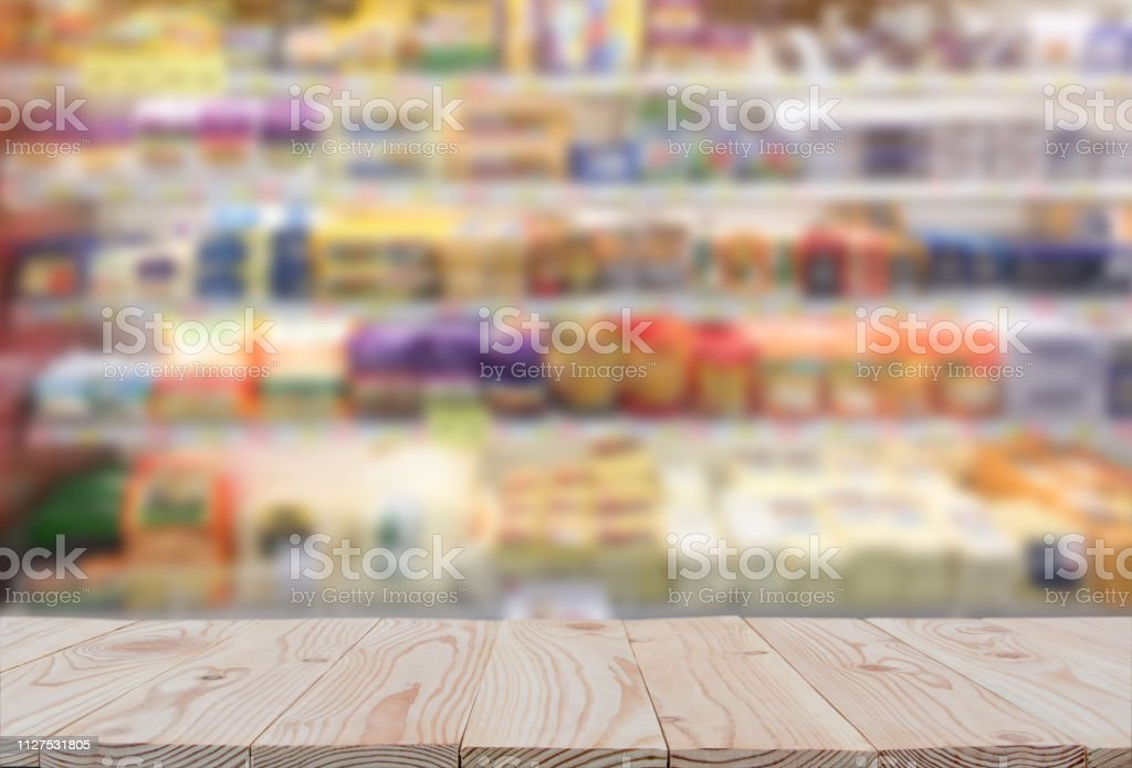 Empty wooden board table top on of blurred supermarket background....