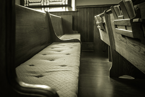 An empty wooden church pew with bibles. Photography in black and white with a horizontal orientation.