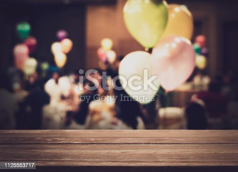 istock Empty wooden counter with blurred people in the banquet room with colorful balloon. 1125553717