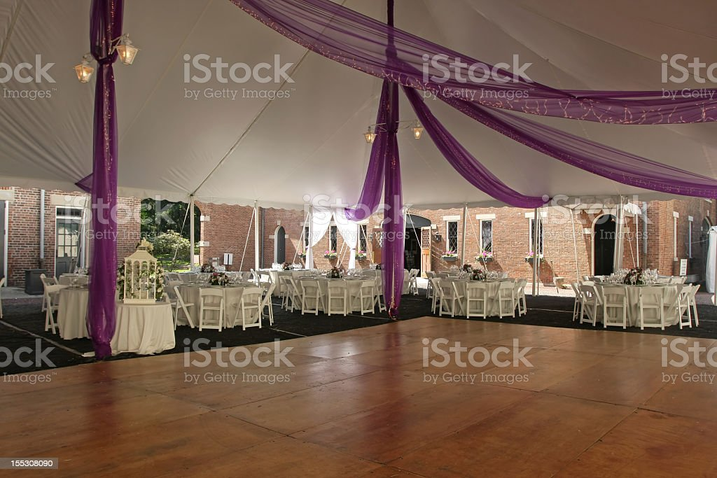 Empty wooden dance floor inside wedding marquee with tables stock photo