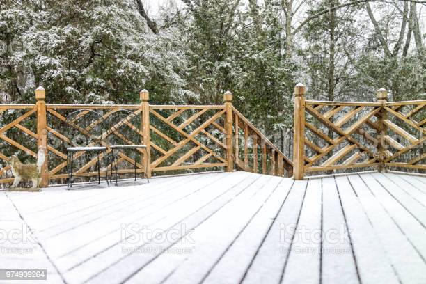 Photo of Empty wooden deck of house with statue decorations, chairs, staircase down on backyard in neighborhood with snow covered wood floor during blizzard white storm, snowflakes falling in Virginia suburb