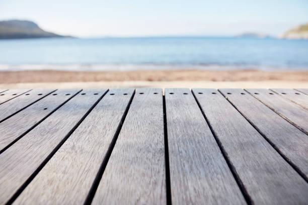 tomma trä däck tabellen på suddiga bakgrunden för havet och stranden - solar panel bildbanksfoton och bilder