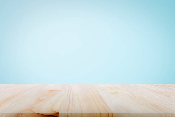 Empty wooden deck table over light blue wallpaper background for present product. stock photo