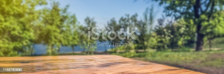 989111446istockphoto Empty wooden deck table with park blur background. 1153782690